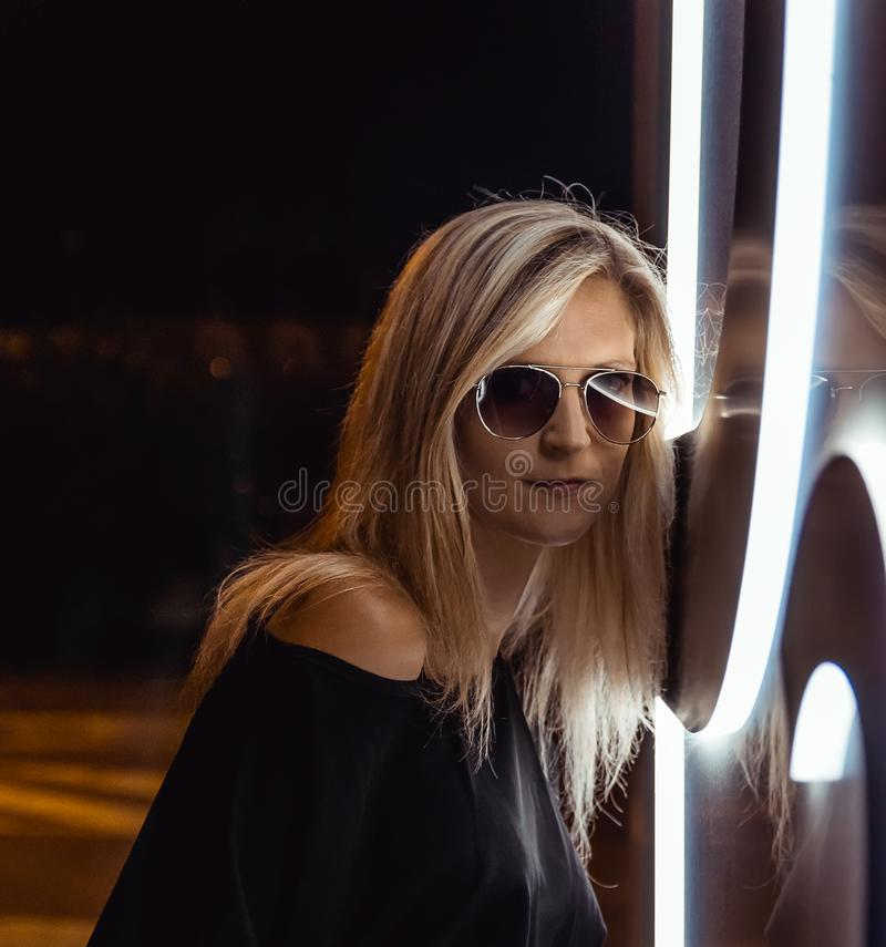 Portrait from side of beauty young blonde hair woman with neon light and sunglasses. Night life.  royalty free stock photo