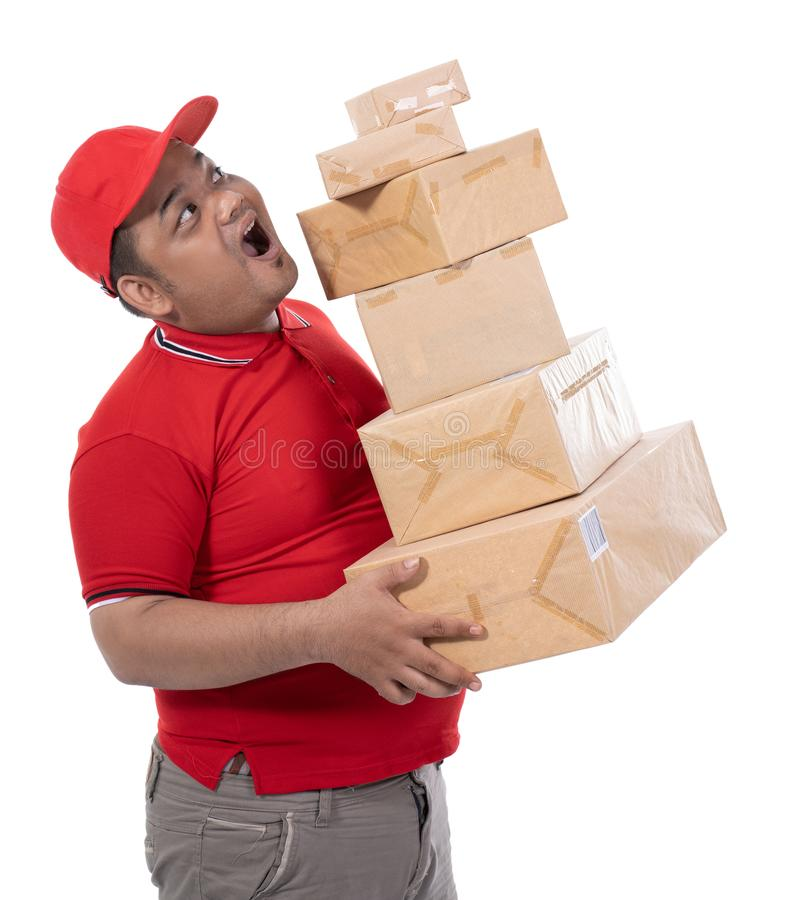 Portrait of side view delivery man struggling to lift many boxes royalty free stock images