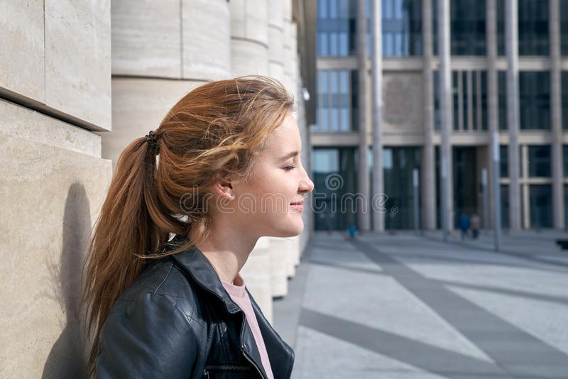 Portrait with the side of young modern girl in a leather jacket basking in the sun on the background of modern urban architecture royalty free stock photo