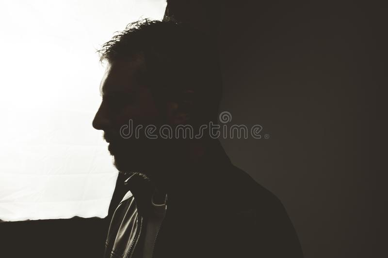 Portrait of a silhouette of a guy in a studio. Dramatic photo stock photography