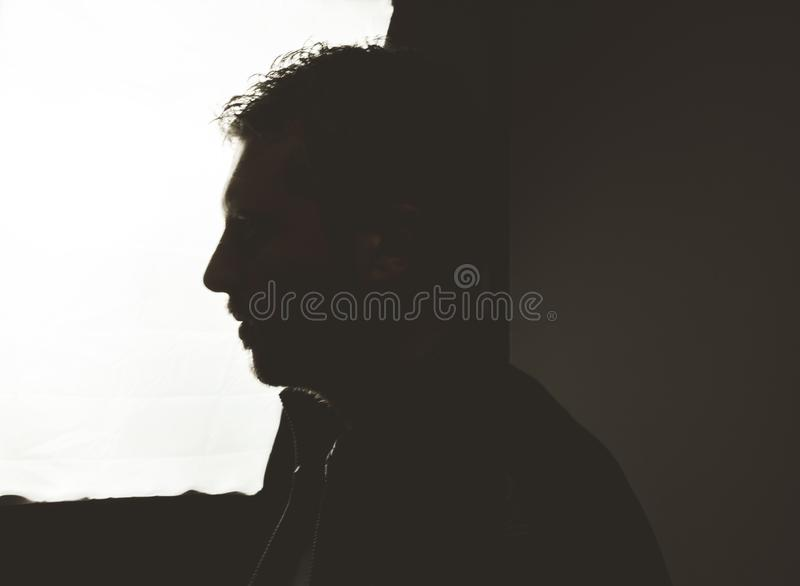 Portrait of a silhouette of a guy in a studio. Dramatic photo stock photos