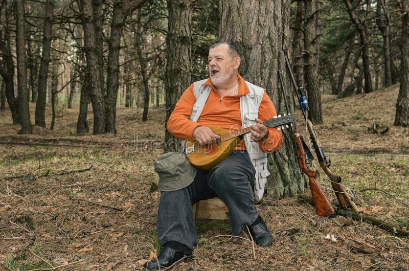 Portrait of singing senior hunter resting in evening forest and playing mandolin. Outdoor portrait of singing senior hunter resting in evening forest and playing stock image
