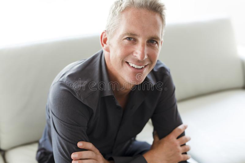 Portrait of single 40s man sitting in sofa. A Portrait of single 40s man sitting in sofa royalty free stock photo