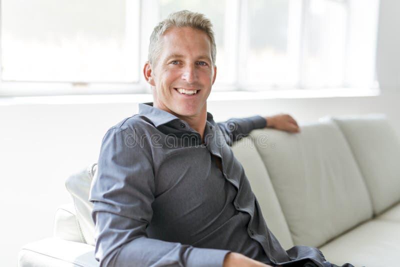 Portrait of single 40s man sitting in sofa. A Portrait of single 40s man sitting in sofa stock photos