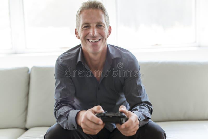 Portrait of single 40s man sitting in sofa play video game. A Portrait of single 40s man sitting in sofa play video game stock images