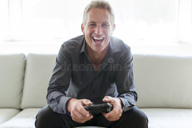 Portrait of single 40s man sitting in sofa play video game. A Portrait of single 40s man sitting in sofa play video game royalty free stock photo