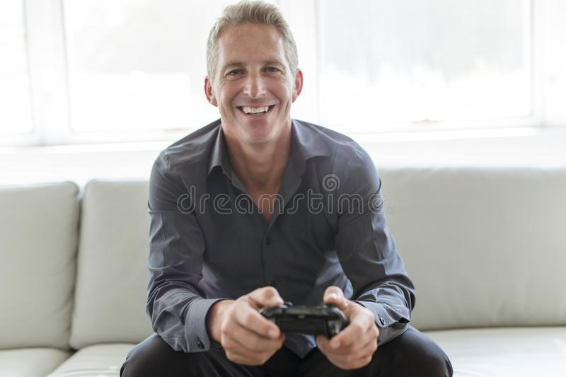 Portrait of single 40s man sitting in sofa play video game. A Portrait of single 40s man sitting in sofa play video game royalty free stock images