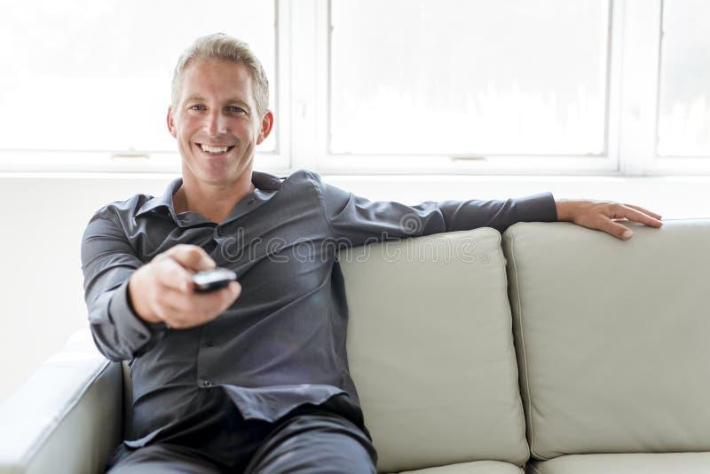 Portrait of single 40s man sitting in sofa tv remote. A Portrait of single 40s man sitting in sofa with tv remote stock photos