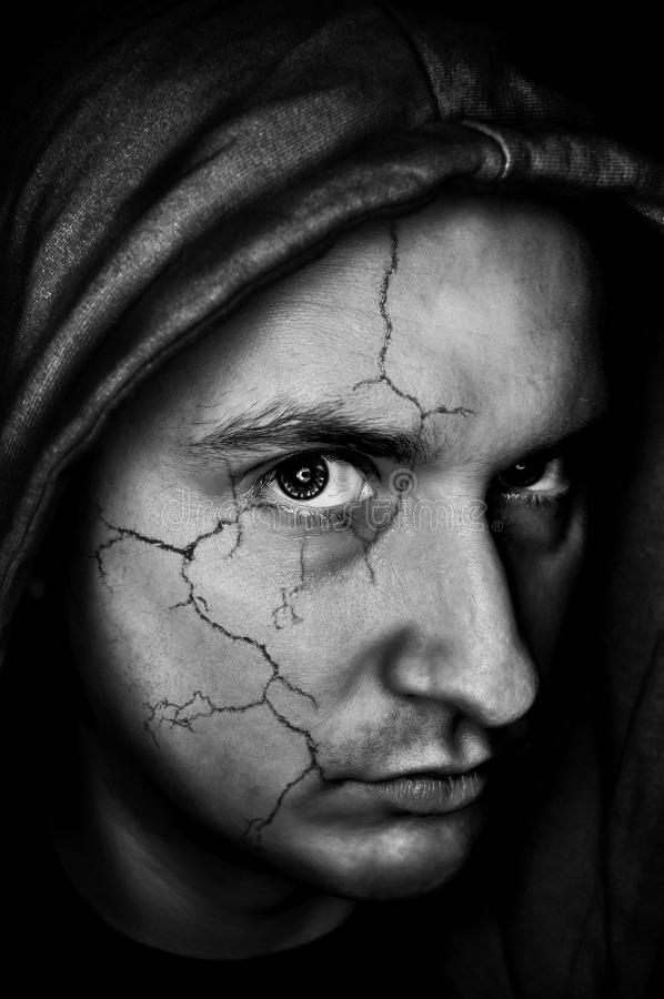 Broken face. Portrait of sinister,spooky looking man with cracked skin stock photography