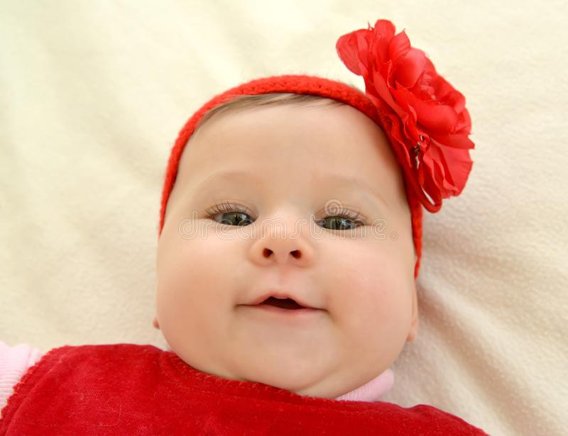 Portrait of the six-months girl with a red flower on the head stock photos