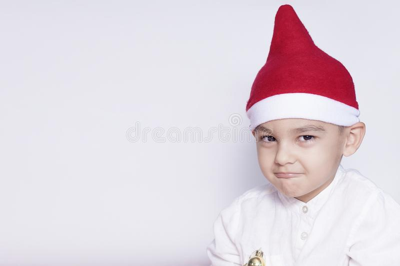 Portrait of a six-year-old boy against the white background. Celebrating Christmas. 6-7 year old kid with Santa hat royalty free stock photography