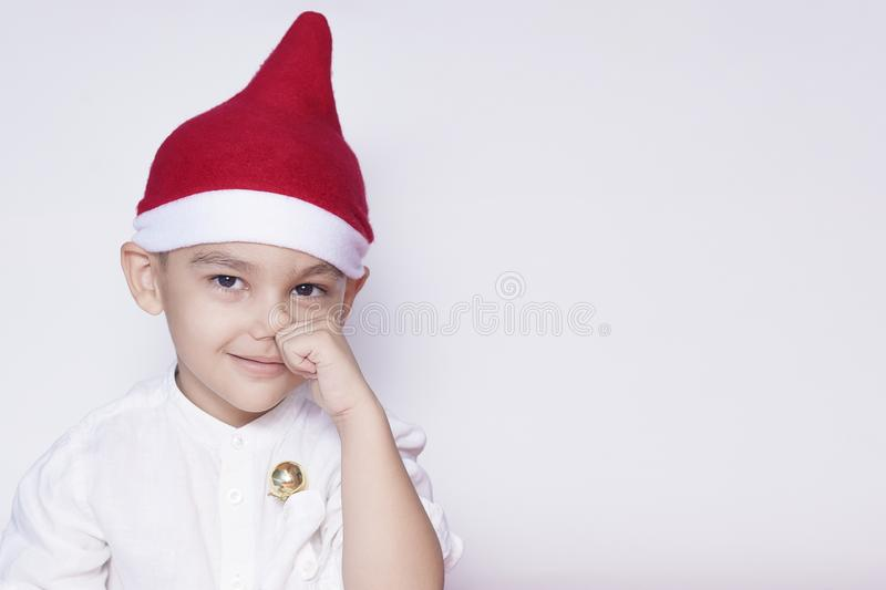Portrait of a six-year-old boy against the white background. Celebrating Christmas. 6-7 year old kid with Santa hat stock photos