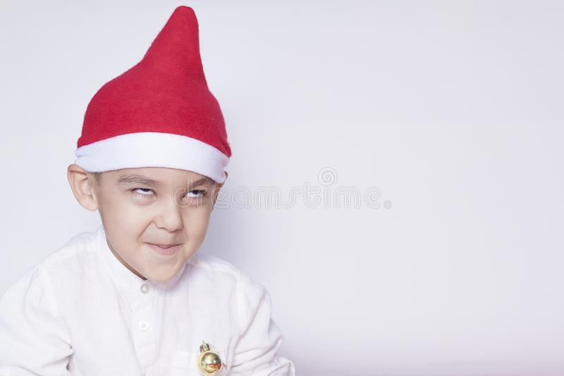 Portrait of a six-year-old boy against the white background. Celebrating Christmas. 6-7 year old kid with Santa hat royalty free stock photo