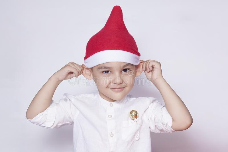 Portrait of a six-year-old boy against the white background. Celebrating Christmas. 6-7 year old kid with Santa hat royalty free stock images