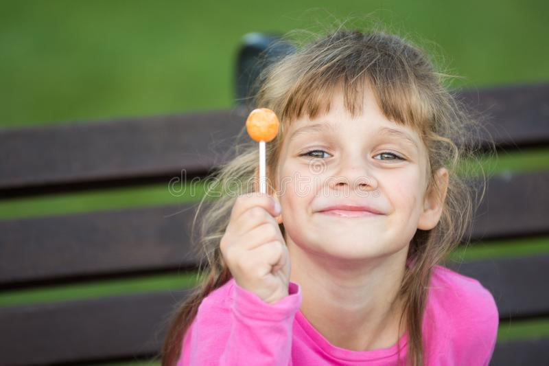 Portrait of a six-year-old cheerful girl who holds a lollipop in her hand. And looks pleased at the frame royalty free stock photo