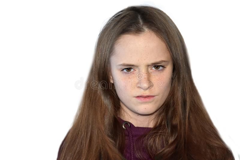 Portrait of a skeptical looking teenage girl. Teenage girl with long brown hair and many freckles looking skeptically royalty free stock photo