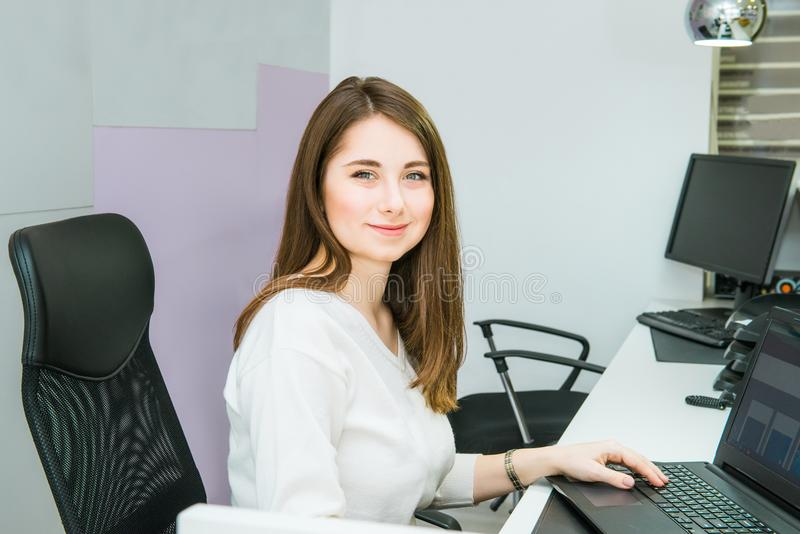 Portrait of skilled administrative manager working on laptop computer in office satisfied with occupation, young female receptioni royalty free stock image