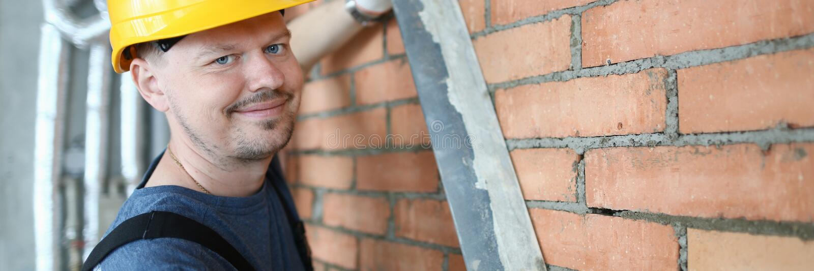 Smiling construction master. Portrait of skilled man using special equipment to remove bigger mass of concrete smart male need. Cheerful builder making brick stock image