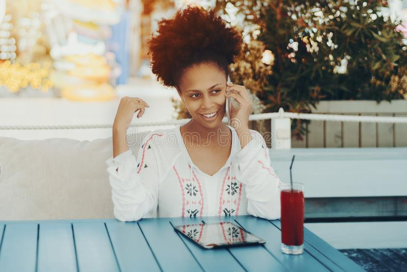 black lady with smartphone in cafe outdoor royalty free stock photo