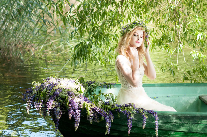 Portrait of slavic or baltic woman with wreath sitting in boat with flowers. Summer stock images