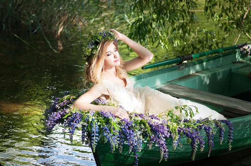 Portrait of slavic or baltic woman with wreath sitting in boat with flowers. Summer. Portrait of slavic or baltic woman with wreath sitting in boat with flowers royalty free stock photos