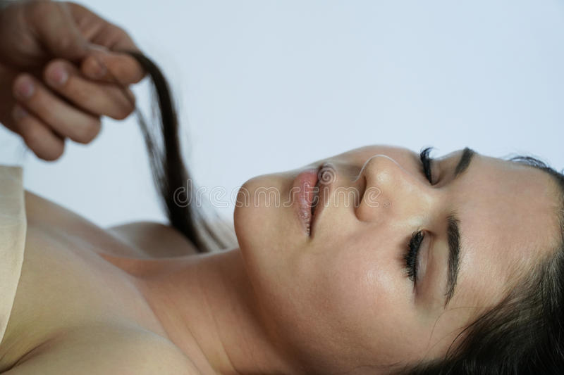 Portrait of a sleeping happy girl. A man`s hand holds a curl of a girl`s hair. Morning awakening. Back of a blurred white backgr stock photography