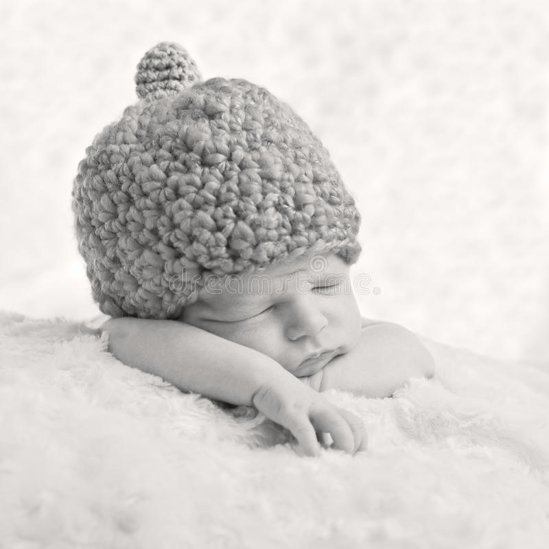 Portrait of a sleeping newborn baby. In a knitted hat ( black and white stock image