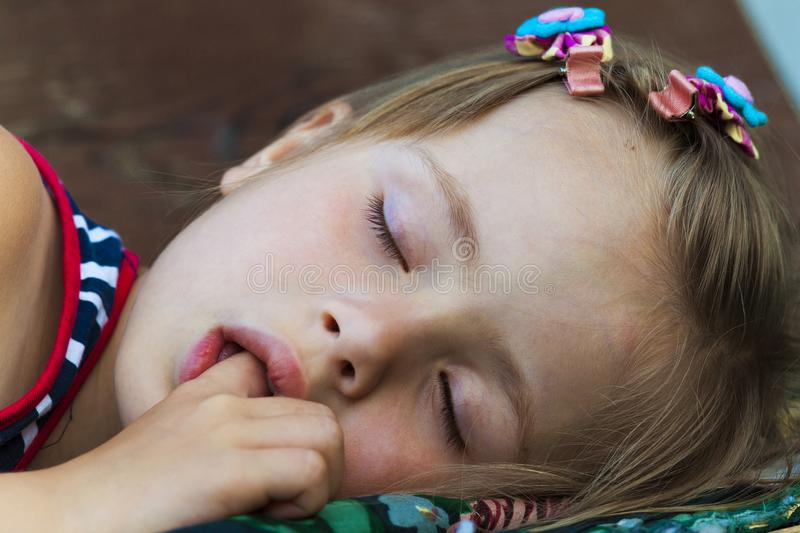 Portrait of sleeping pretty child girl who sucks her finger while sleeping. Children healthcare and well-being concept. Picture of peaceful adorable kid in bed stock photo