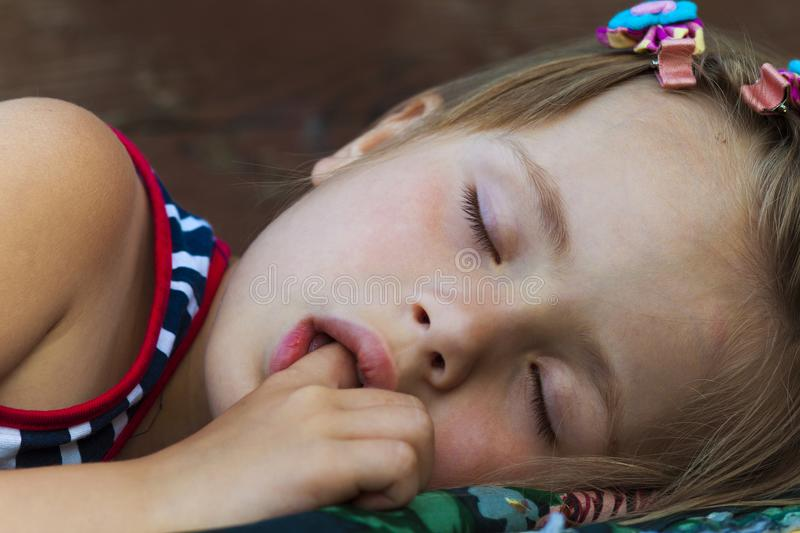 Portrait of sleeping pretty child girl who sucks her finger while sleeping. Children healthcare and well-being concept. Picture of peaceful adorable kid in bed royalty free stock photos