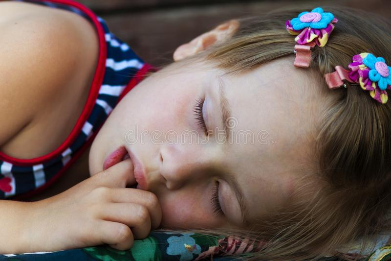 Portrait of sleeping pretty child girl who sucks her finger while sleeping. royalty free stock photography