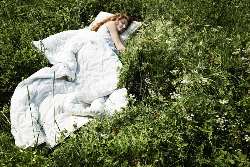 Portrait of the sleeping young woman on a meadow. Shooting on the nature stock photo