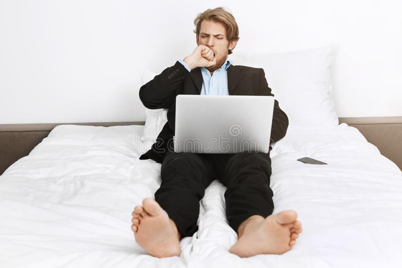Portrait of sleepy attractive mature company director lying in bed, closing mouth with hand with hand while yawning stock images