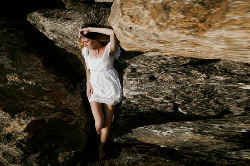 Portrait of slender young woman on stones near the sea royalty free stock photo