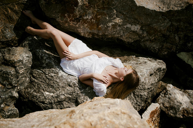 Portrait of slender young woman on stones near the sea stock photo