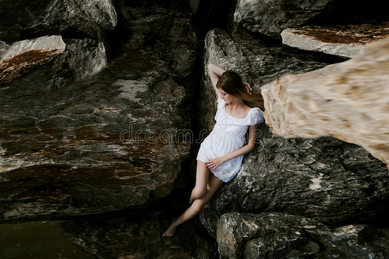 Portrait of slender young woman on stones near the sea royalty free stock photography