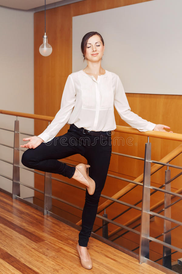 Portrait of slim fit sporty young white Caucasian business woman meditating doing yoga exercises. Portrait of slim fit sporty young white Caucasian business stock images