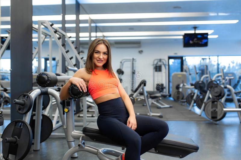 Portrait of slim handsome young woman relax in gym after hard training royalty free stock images