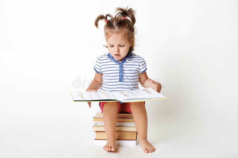 Portrait of small adorable child sits on pile of books, holds in royalty free stock photos