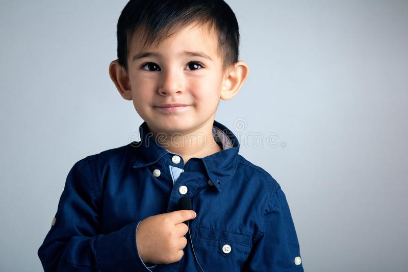 Portrait of a small boy with a microphone as a button in his hands in a role of a telecom operator stock image