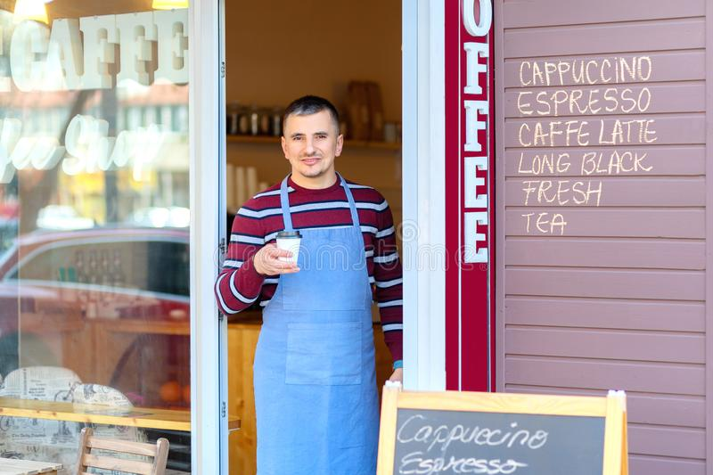 Portrait of small business coffee shop owner smiling and standing in front of shop serving a takeaway coffee royalty free stock photography