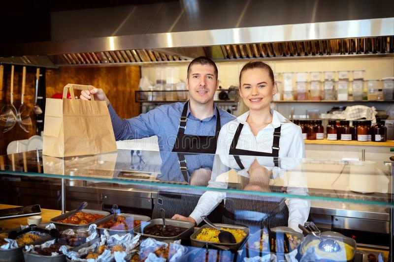 Portrait of small business owner smiling behind counter inside eatery holding food order for home delivery. Portrait of small business owner smiling behind royalty free stock photo