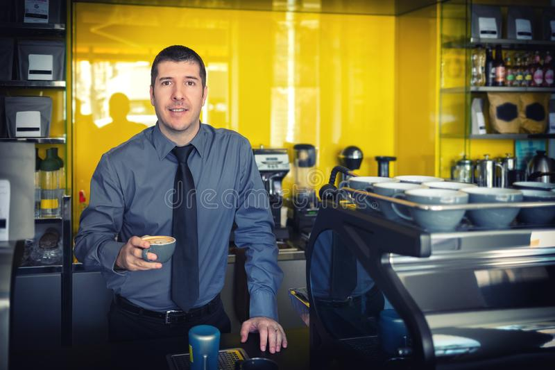 Portrait of small business owner smiling and standing behind counter inside coffee shop holding cup of coffee. Portrait of small business owner smiling and royalty free stock photography