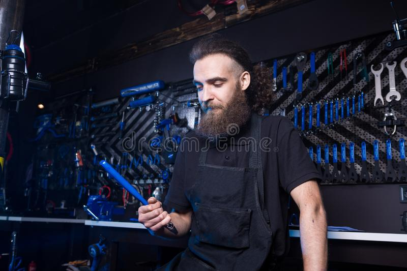 Portrait of small business owner of young man with beard. Guy bicycle mechanic workshop worker sitting with tool in his hand in a stock photos
