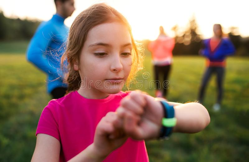 A portrait of small girl with large group of people doing exercise in nature. royalty free stock photography