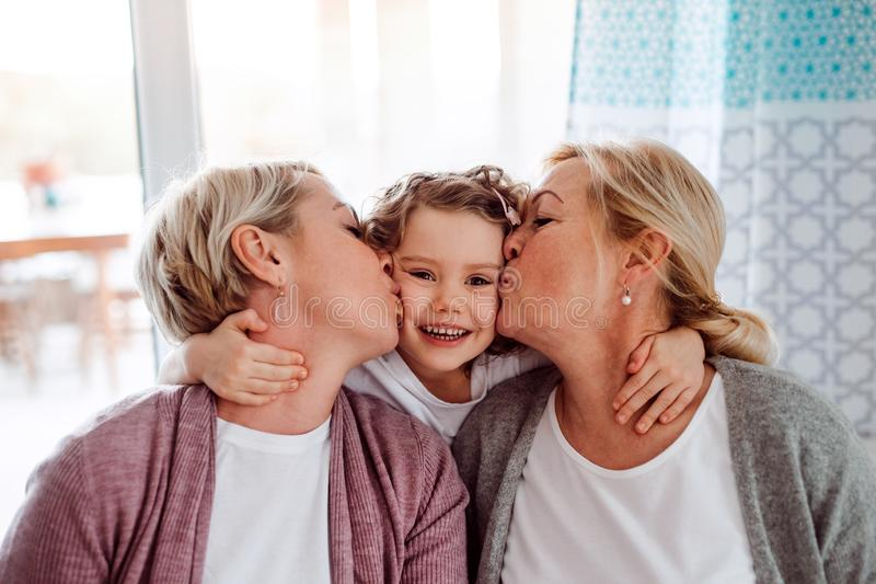 A portrait of small girl with mother and grandmother at home, kissing. royalty free stock photography