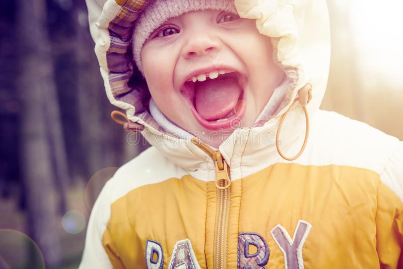 Portrait of small happy child in hood and warm clothes in early spring. Laughing baby in nature stock image