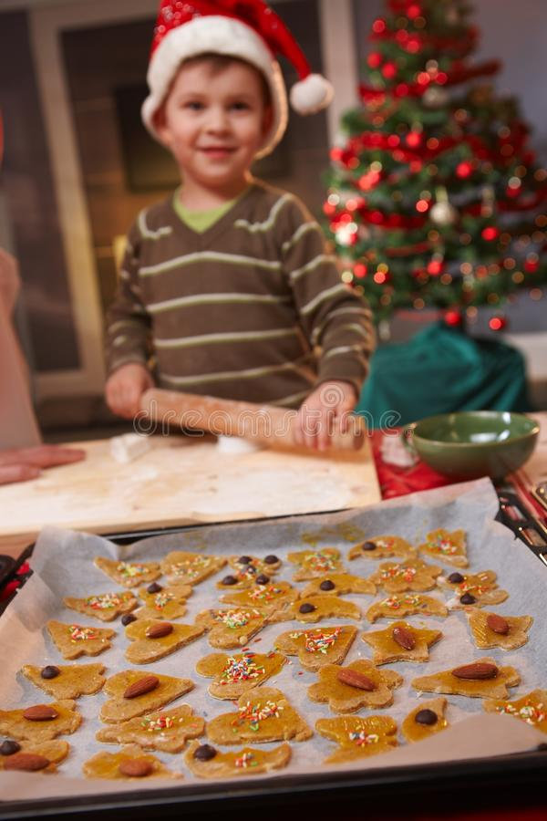 Portrait of small kid doing christmas baking. Cake in focus, child smiling at camera stock photo