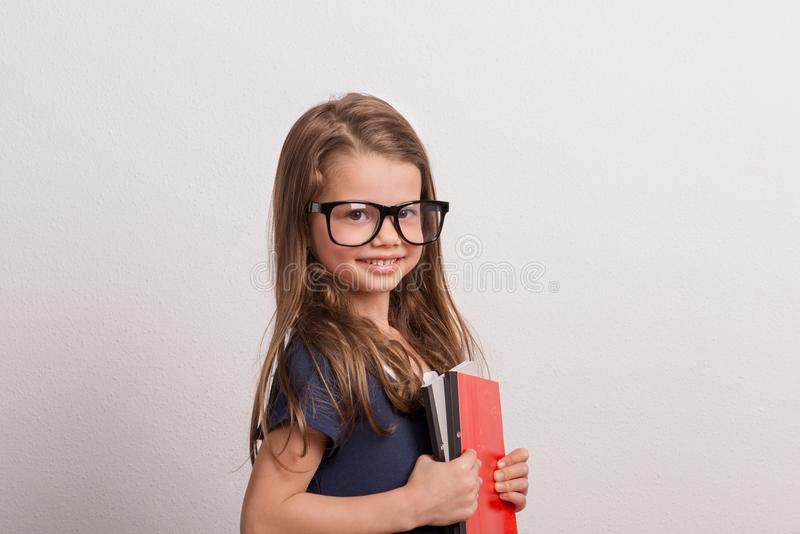 Portrait of a small schoolgirl with big glasses in a studio, holding notebooks. royalty free stock photography