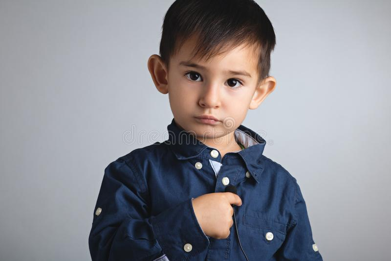 Portrait of a small serious boy with a microphone as a button in a role of a telecom operator stock photography