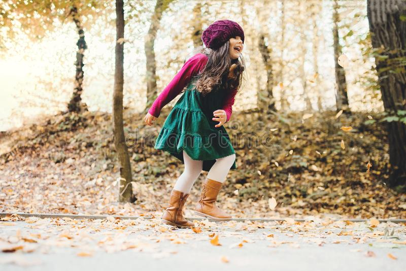 A portrait of a small toddler girl running in forest in autumn nature. stock images